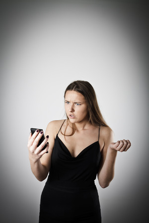 disappointed: Disappointed and irritated woman talking on the phone. Young woman is doing something. Stock Photo