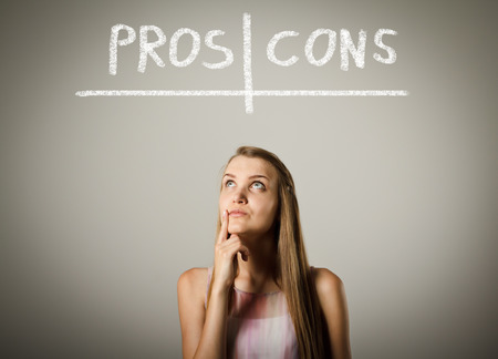 hesitation: Girl is thinking. Pros and cons concept. Young woman is doing something. Stock Photo