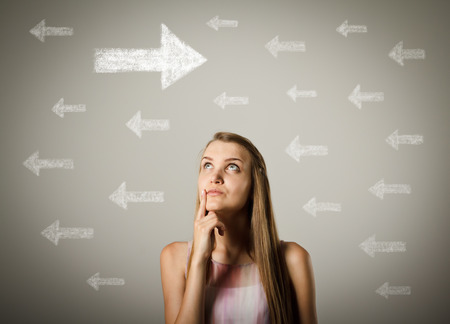 hesitation: Young woman is looking at arrows. Girl is full of doubts and hesitation. Young woman is doing something. Stock Photo