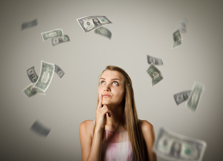 hesitation: Girl and falling dollar banknotes. Currency and lottery concept. Young woman is doing something.