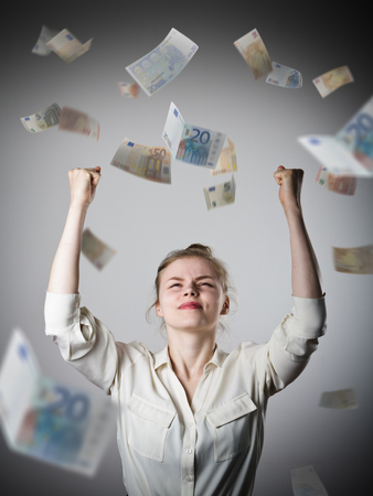 exult: Rejoicing. Young slim woman and falling Euro banknotes. Success, currency and lottery concept.