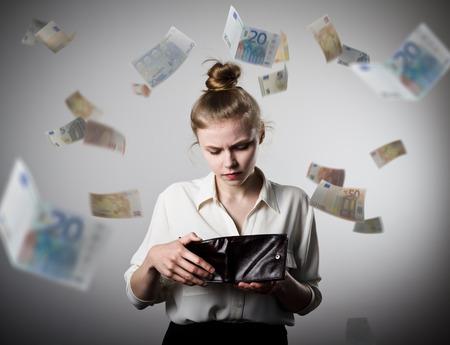 Worried slim woman is looking in a wallet. Euros are falling.