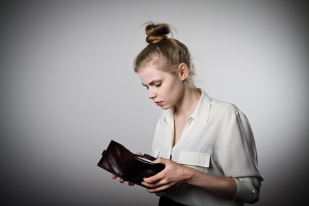 Worried slim woman is looking at an empty wallet Stock Photo