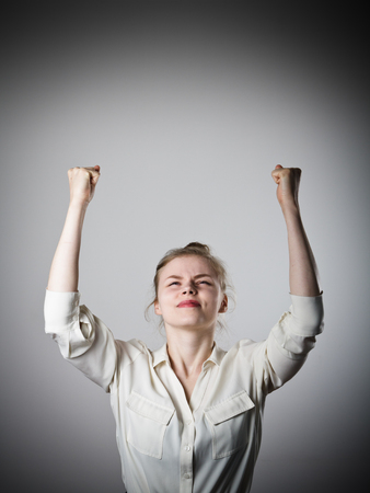 exult: Rejoicing young slim woman. Success and winner concept. Stock Photo