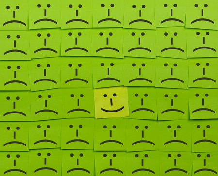sticky notes: Happy and unhappy concept. Background of green sticky notes. Happy sticky note is among unhappy sticky notes.