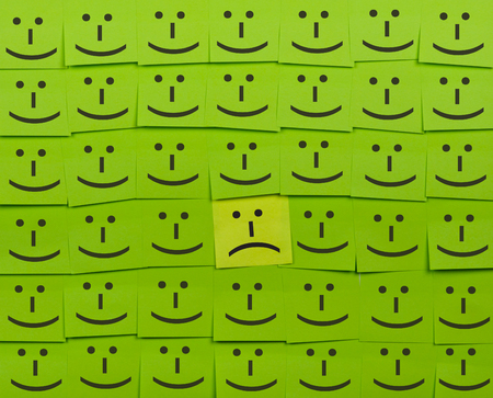 sticky note: Unhappy and happy concept. Background of green sticky notes. Unhappy sticky note is among happy sticky notes. Stock Photo