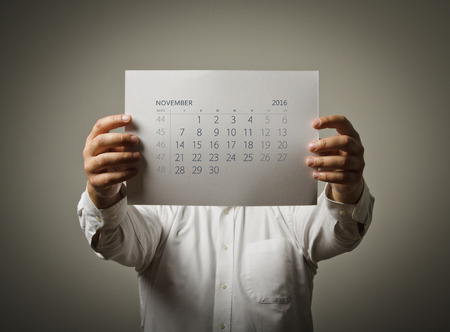 sixteen: Man is holding November calendar of the year two thousand sixteen. Stock Photo