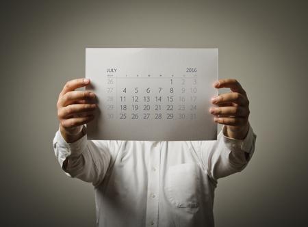 calendario julio: El hombre está sosteniendo el calendario de julio del año dos mil dieciséis años. Foto de archivo
