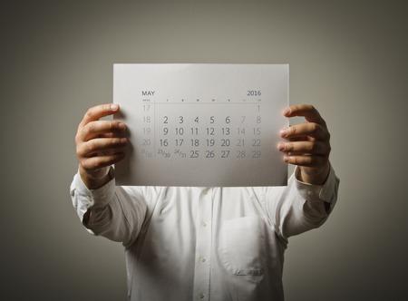 sixteen: Man is holding May calendar of the year two thousand sixteen. Stock Photo