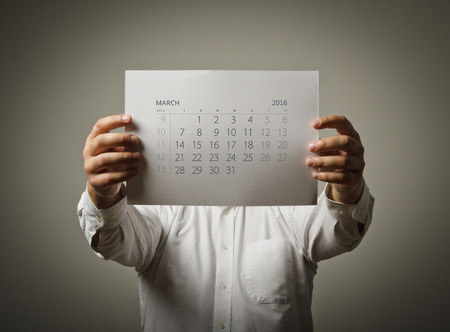 sixteen: Man is holding March calendar of the year two thousand sixteen.