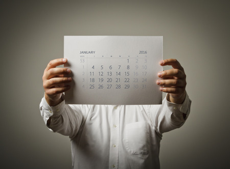 sixteen: Man is holding January calendar of the year two thousand sixteen.