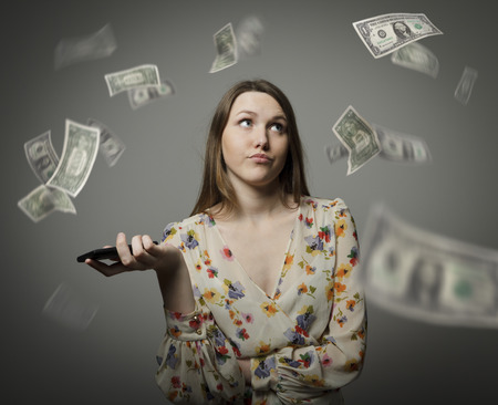 Young woman and falling dollar banknotes. Consumerism concept.
