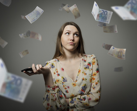 Young woman and falling Euro banknotes. Consumerism concept. Stock Photo