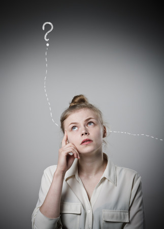 hesitation: Girl in white full of doubts and hesitation. Girl and question mark above her head. Young slim woman. Stock Photo
