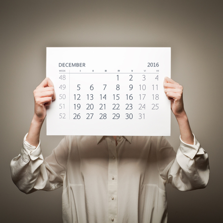 sixteen: Woman is holding December calendar of the year two thousand sixteen.