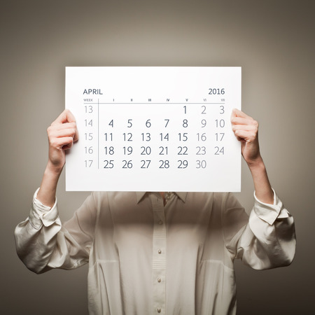 sixteen: Woman is holding April calendar of the year two thousand sixteen.