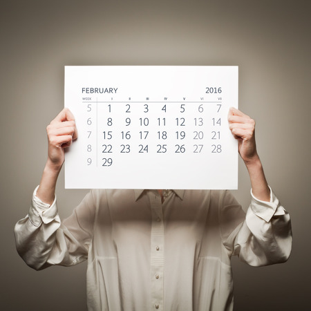 sixteen: Woman is holding February calendar of the year two thousand sixteen. Stock Photo