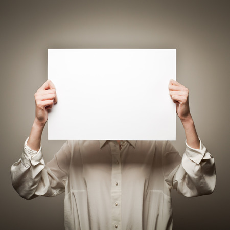 incognito: Woman is holding white paper in her hands Stock Photo