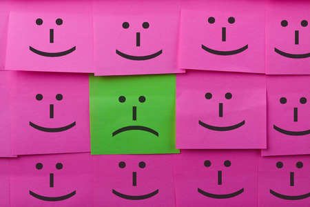 sticky notes: Unhappy and happy concept. Background of sticky notes. Green sticky note is among pink sticky notes.