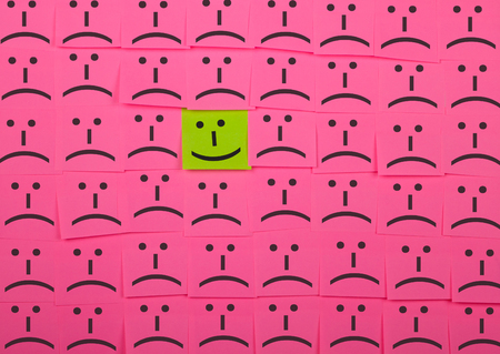 envy: Happy and unhappy concept. Background of pink sticky notes. Happy sticky note is among unhappy sticky notes.