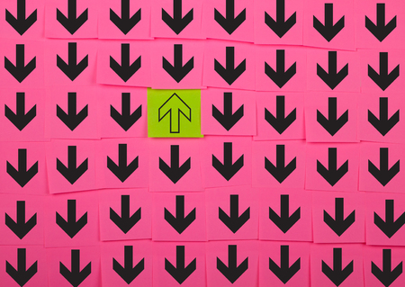 reverse: Arrows. Opposite direction concept. Background of pink sticky notes.