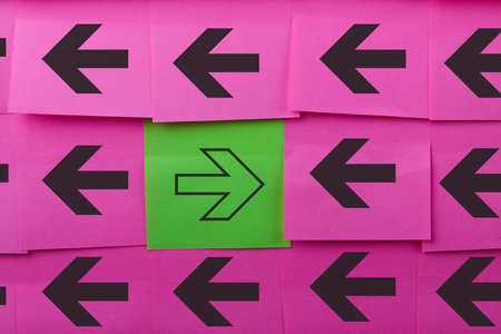 opposing: Arrows. Opposite concept. Background of pink sticky notes.