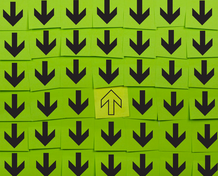 oppose: Arrows. Opposite direction concept. Background of green sticky notes. Stock Photo