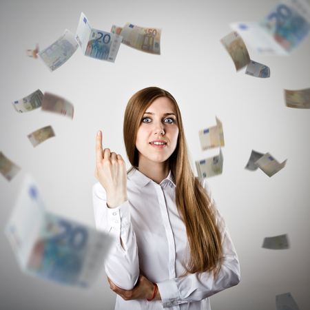 exult: Pointing. Woman in white and falling Euro banknotes. Currency and lottery concept. Stock Photo