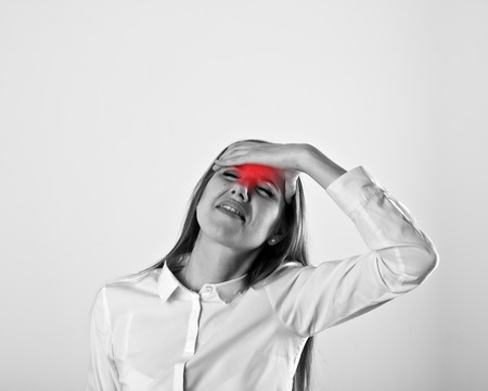 chagrin: Woman in white is suffering from headache. Pain concept. Stock Photo