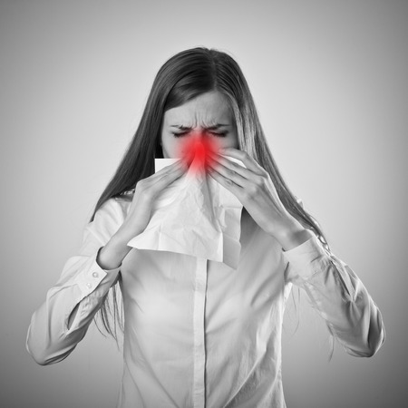 rheum: Young woman in white is sneezing.