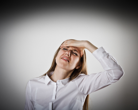 Woman in white is suffering from headache. Pain concept. Stock Photo