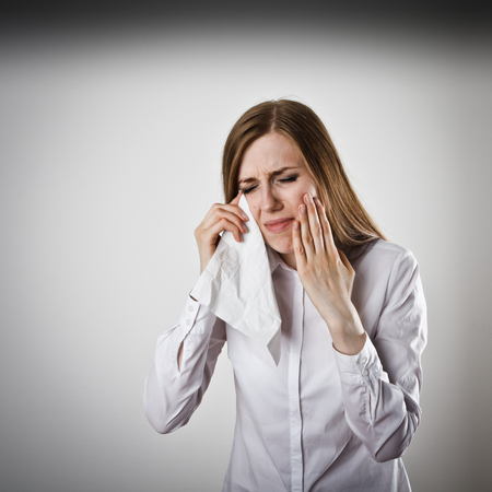 handkerchief: Sad and Unhappy woman in white. Tears welled up in her eyes. Crying concept.