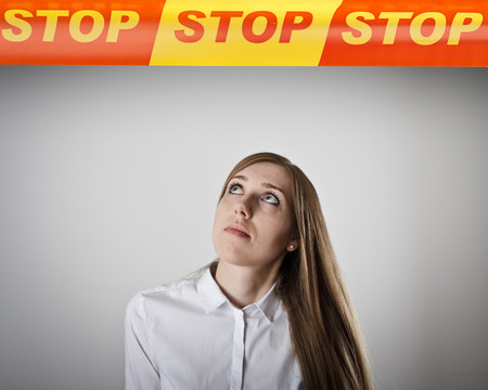 restricted area: Young slim woman and STOP line over her head. Restricted area concept. Stock Photo
