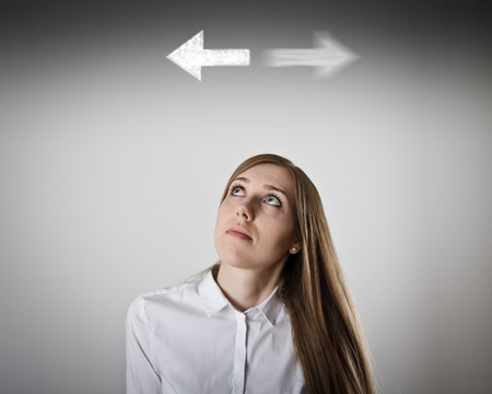 Woman in white has to decide between two directions. Girl in white full of doubts and hesitation.