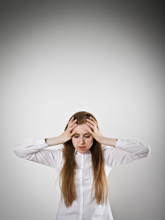 chagrin: Woman in white is suffering from headache. Stock Photo