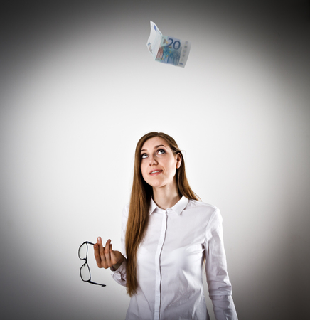 Woman in white and falling twenty Euro banknote.