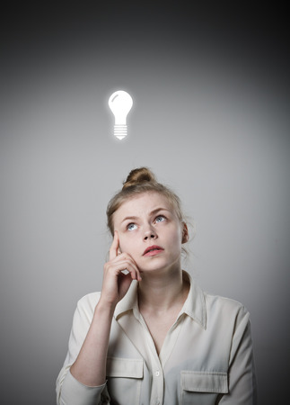 Girl in white having an idea with light bulb over her head. Young slim woman. Stock Photo