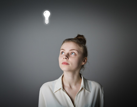 unintelligent: Girl in white having an idea with light bulb over her head.