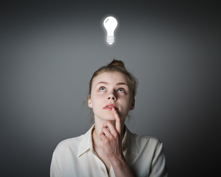 superficial: Girl in white having an idea with light bulb over her head. Young slim woman. Stock Photo