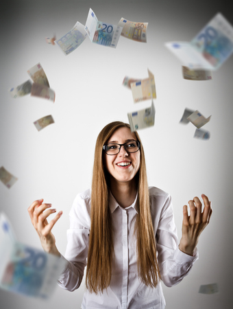 exult: Rejoicing. Woman in white and falling Euro banknotes. Success, currency and lottery concept.