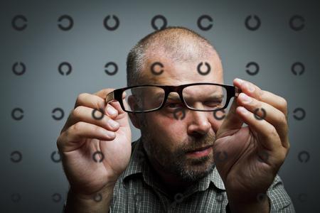 oculista: El hombre está mirando a través de las gafas. Tabla oftalmólogo doctor examen de los puntos oculista.
