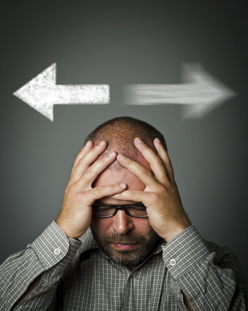 decide: Man has to decide between two directions. Man is full of doubts and hesitation. Stock Photo