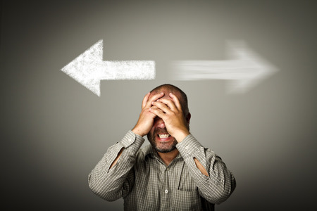 deliberation: Man has to decide between two directions. Man is full of doubts and hesitation. Stock Photo