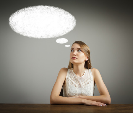Girl in white is having an idea with blank speech bubble over her head. Young woman is doing something.