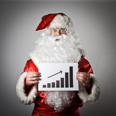 Santa Claus is holding a diagram in his hands. Up concept.