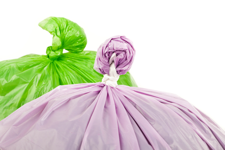 Green and violet garbage bags on white background