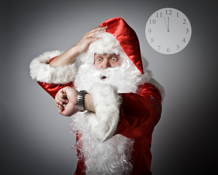 Santa Claus is looking at his wristwatch. Its almost twelve oclock. Concept of being late.