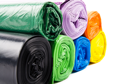 Colored garbage bags on white background