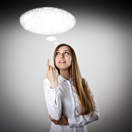 Pointing. Woman in white is having an idea with blank speech bubble over her head. Stock Photo