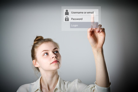 Girl in white is pushing the virtual button. Login and password concept. Young slim woman. Stock Photo